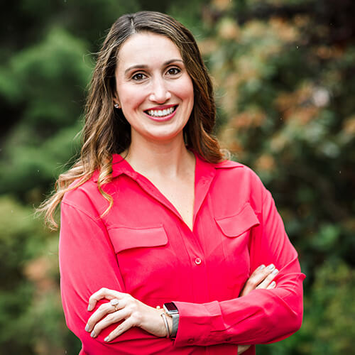 Headshot of Dr. Patra Alatsis - an orthodontist in Gig Harbor and Tacoma - smiling outdoors wearing a red blouse